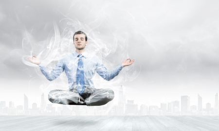 Young businessman sitting in lotus pose and meditating photo