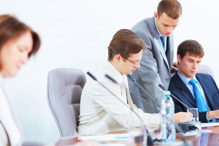 Image of four businesspeople discussing at meeting photo