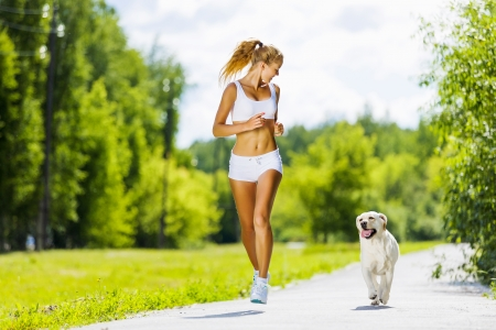 leisure sports: Young attractive sport girl running with dog in park