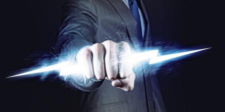 r�sistance: Homme d'affaires tenant la foudre en puissance et contr�le poing