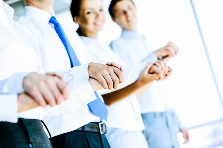Image of group of businesspeople holding arms together  Teamwork