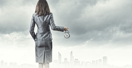 Back view of businesswoman holding alarm clock against city background photo