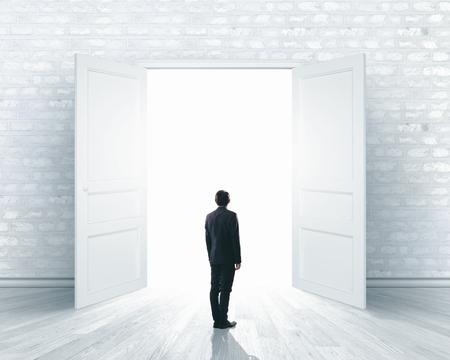 out door: Image of businessman standing in front of opened door