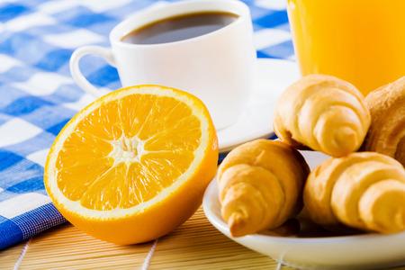 クロワッサンとコーヒーの朝食のテーブルの上のカップ