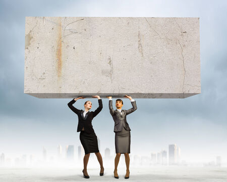 cohesion: Image of two businesswomen holding stone above head  Partnership and cohesion