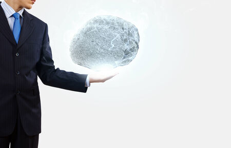 burdensome: Businessman in suit huge holding stone in palm