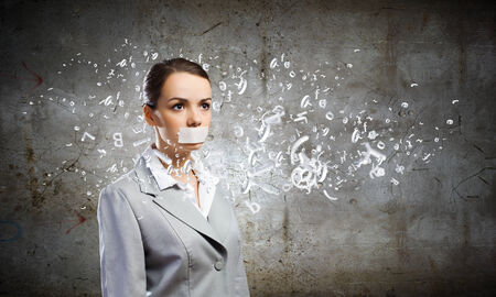 voiceless: Young speechless businesswoman with adhesive tape on mouth Stock Photo