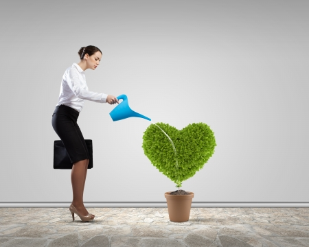 Young attractive businesswoman watering plant in pot with can photo