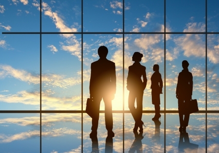 Silhouettes of businesspeople standing against panoramic office window photo