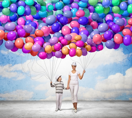 Image of mother and son holding bunch of colorful balloons Stock Photo