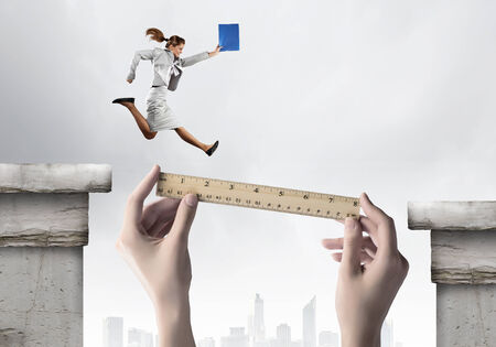 Businesswoman jumping over gap  Risk and challenge concept photo