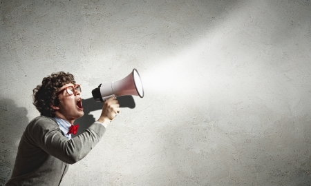 loudly: Portrait of young man shouting loudly using megaphone Stock Photo