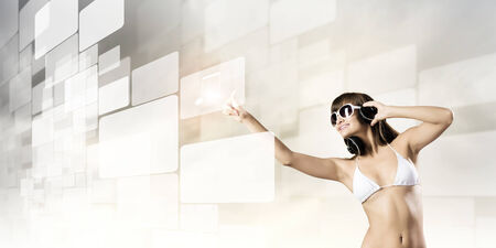Young attractive girl in bikini wearing headphones touching media icon photo