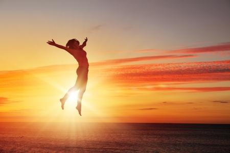Silhouette de la danseuse sautant contre la ville à la lumière du lever du soleil