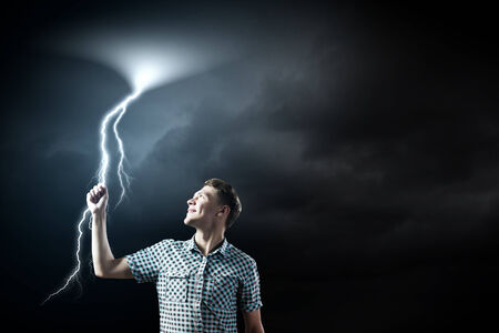 Young man touching illustration of lightning in sky illustration