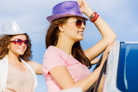 Young pretty women standing near white car at side of road photo