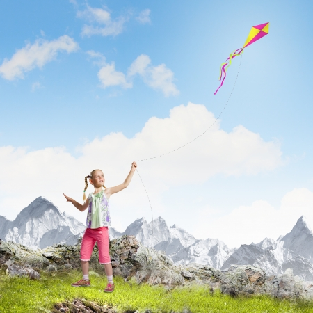 Image of little girl playing with kite at meadow photo