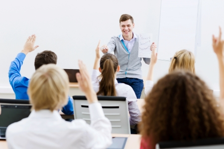 Young teacher in classroom standing in front of class Stock Photo