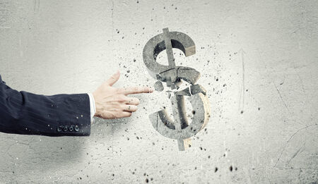 Businessman breaking dollar stone symbol with finger touch