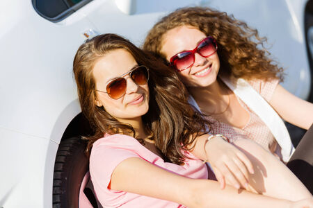 Young pretty women sitting near white car at side of road photo