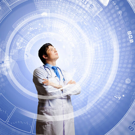 Image of young thoughtful doctor looking at media screen