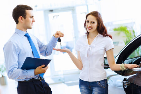 Attractive woman at car salon with consultant choosing a car photo