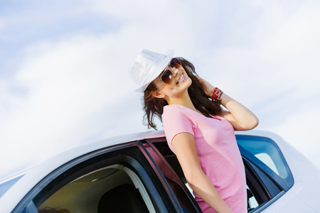 Young pretty woman leaning out of car window photo