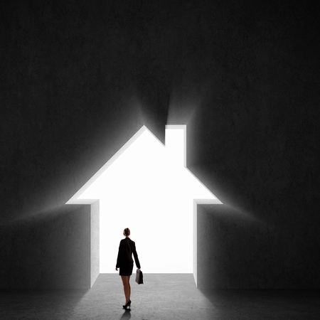 Image of businesswoman silhouette standing with back against house photo