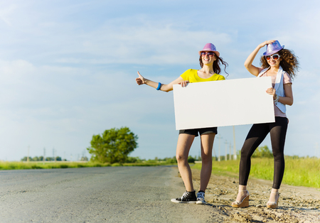 hitch hiker: Two pretty young girls standing aside road with blank white banner