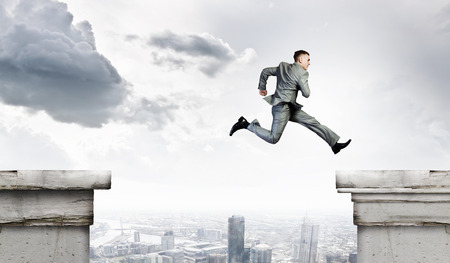 Image of young businessman jumping over gap in bridge photo
