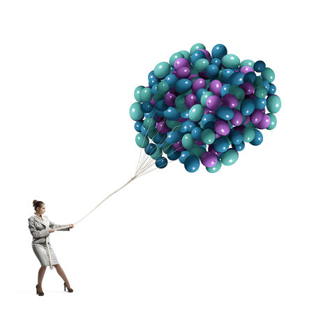 Young businesswoman pulling bunch of colorful balloons photo