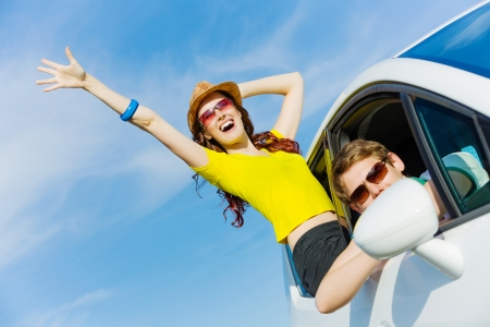 Young people leaning out of car and waving happily photo
