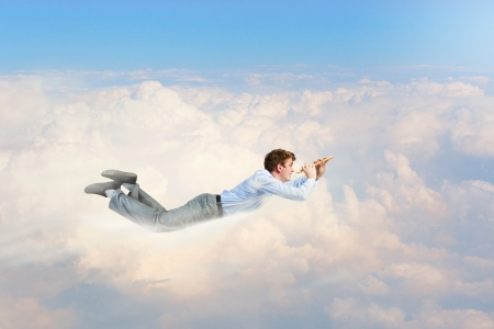 Young businessman flying in sky and playing fife photo