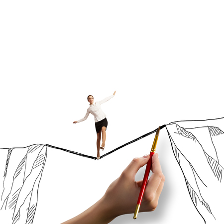 Young businesswoman walking on rope above mountain gap photo