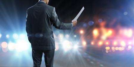 Achteraanzicht van zakenman spreker staande op podium in lichten