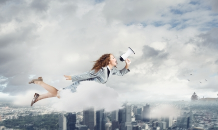 Young pretty businesswoman flying in blue sky sreaming in megaphone photo