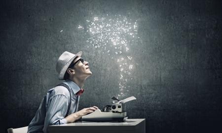 タイプライターで書くメガネで面白い若者 写真素材