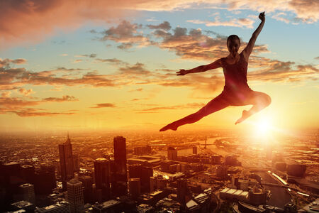 Silhouette of dancer jumping against city in lights of sunrise photo