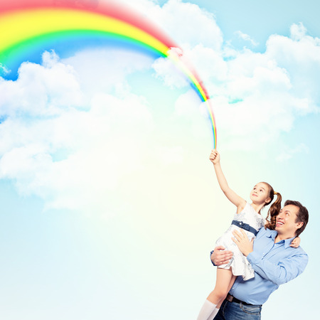 Image of happy father holding on hands daughter ad rainbow Stock Photo