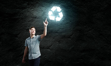 Young handsome man against dark backdrop touching recycle sign photo
