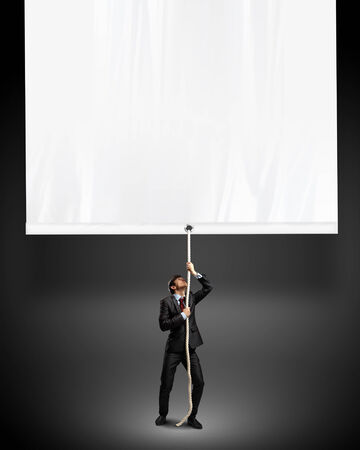 blank banner: Image of young businessman pulling blank banner  Place for text Stock Photo