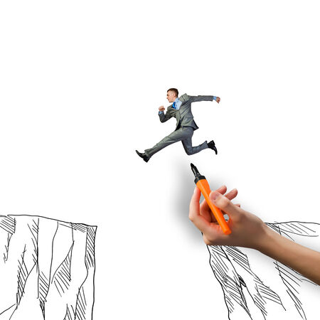 trouble free: Young businessman jumping over drawn mountain gap Stock Photo