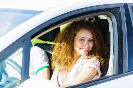 Young pretty woman driving car and leaning out of car window photo