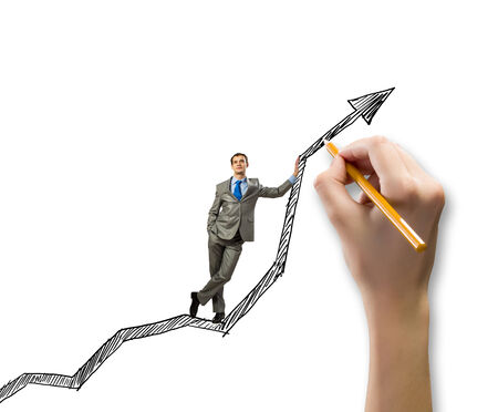 Young businessman standing on drawn graph arrow photo