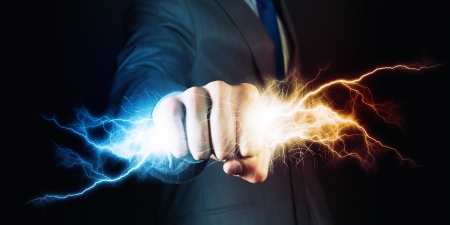 Businessman holding lightning in fist  Power and control