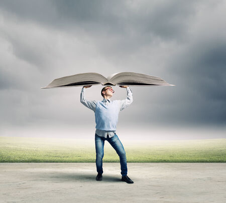 Young man holding huge book above head photo