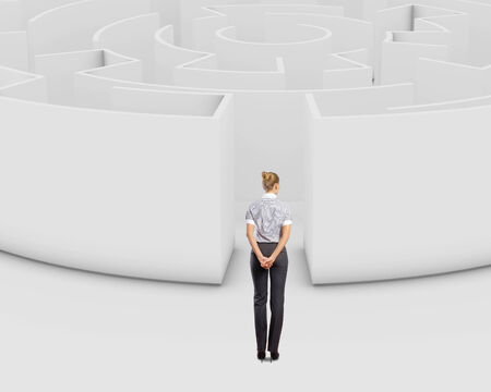 Thoughtful businesswoman standing near the enter of labyrinth photo