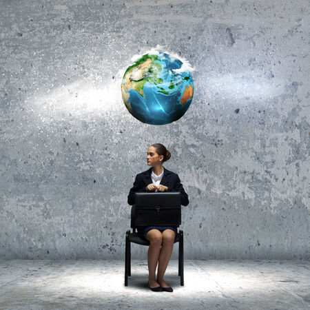 Young upset businesswoman with suitcase sitting on chair  Elements of this image are furnished by NASA photo