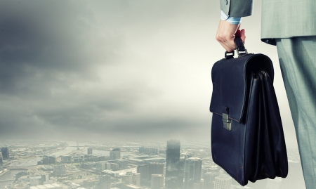 Back view of businessman with suitcase in hand Stock Photo