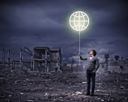 Young man and the symbol of our planet against polluted and ruined landscape photo